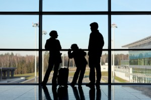 silhouette of mother, father and son with luggage standing near